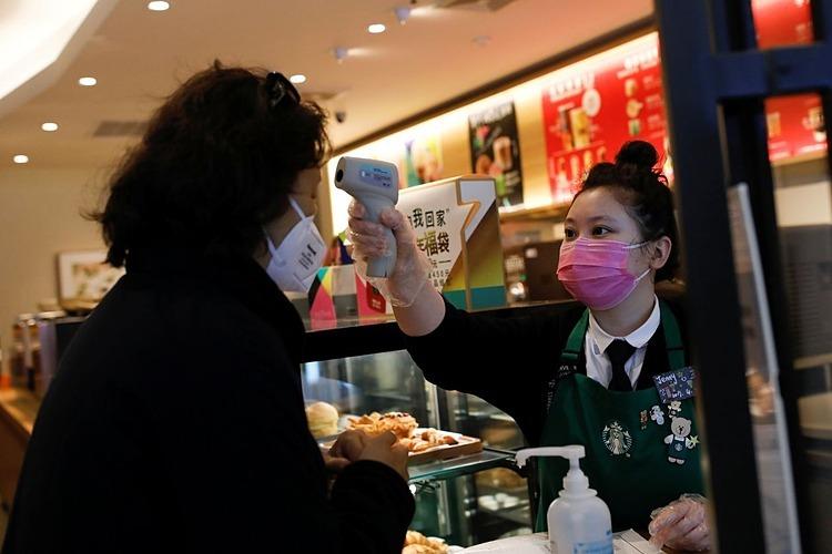 Nhân viên Starbucks kiểm tra thân nhiệt khách hàng tại Bắc Kinh. Ảnh: Reuters