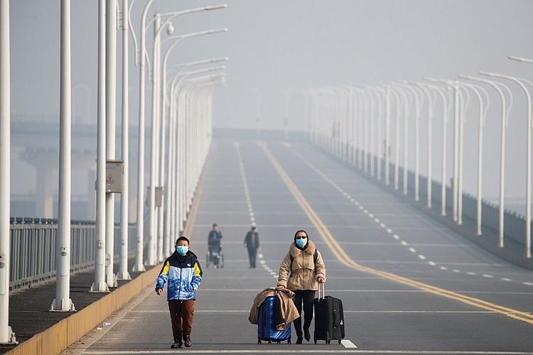 Hai mẹ con đến từ Hồ Bắc đang tiến về trạm kiểm soát cầu Cửu Giang, tỉnh Giang Tây, Trung Quốc. Ảnh: Reuters