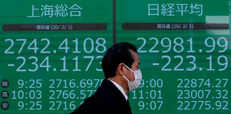 Người đàn ông đi qua bảng điện tử một công ty môi giới ở Tokyo (Nhật Bản). Ảnh: Reuters