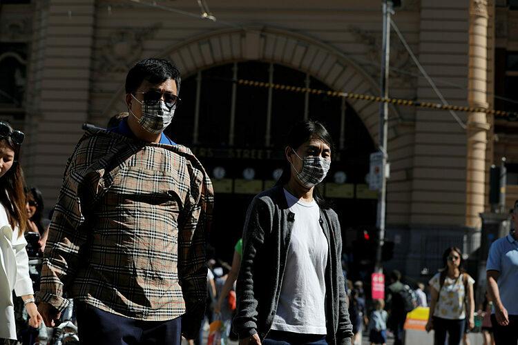 Người dân đi qua nhà ga Flinders Street ở Australia. Ảnh: Reuters