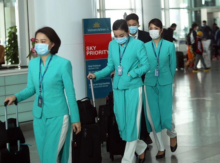 Tiếp viên hàng không đeo khẩu trang trước khi lên máy bay tại sân bay Nội Bài. Ảnh: Gia Chính.