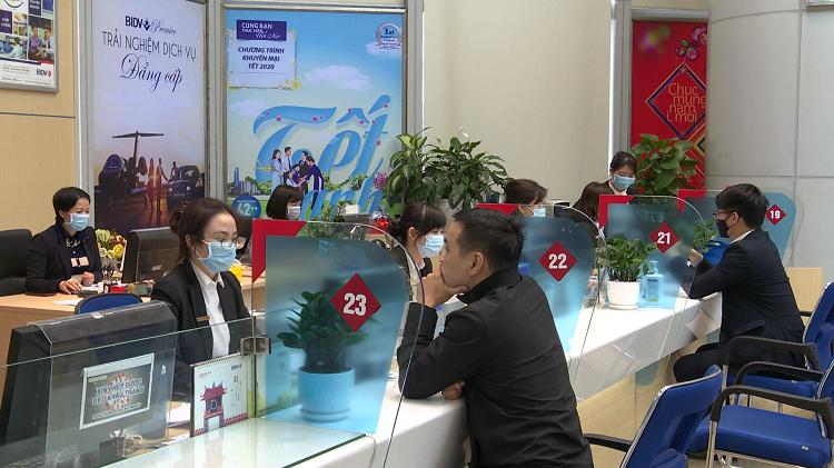 Các nhân viên BIDV đều đeo khẩu trang tại một quầy giao dịch BIDV.