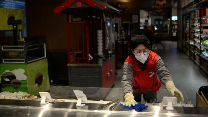 Nhân viên một cửa hàng tại Bắc Kinh lau dọn kệ đồ. Ảnh: Reuters