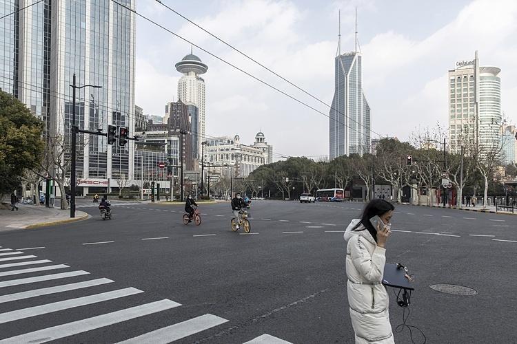 Một phụ nữ cầm laptop đi trên đường phố Nam Kinh, Thượng Hải. Ảnh: Bloomberg