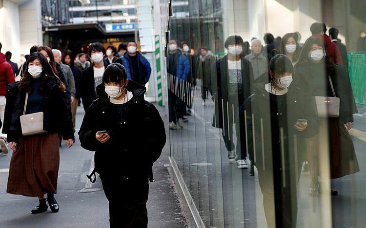 Người Nhật Bản đeo khẩu trang bên ngoài một nhà ga ở Yokohama. Ảnh: Reuters