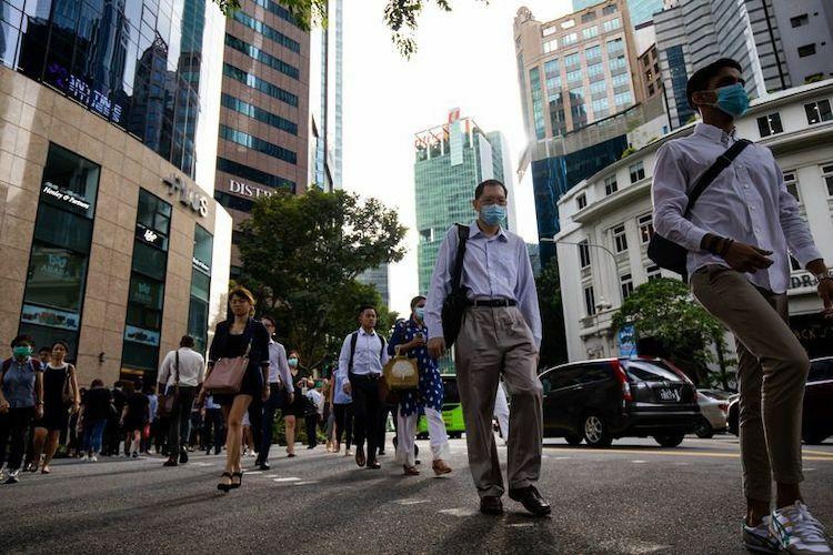 Người dân Singapore đeo khẩu trang trên đường phố tại khu trung tâm tài chính. Ảnh Bloomberg