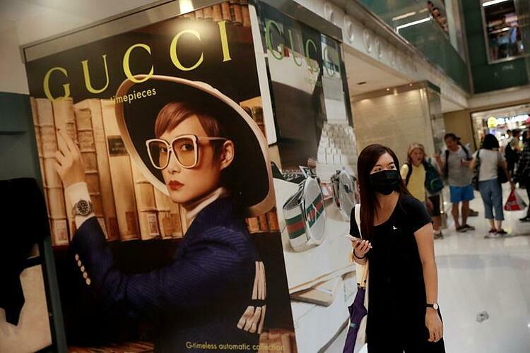 Khách hàng đi qua một biển quảng cáo của Gucci tại Hong Kong (Trung Quốc). Ảnh: Reuters