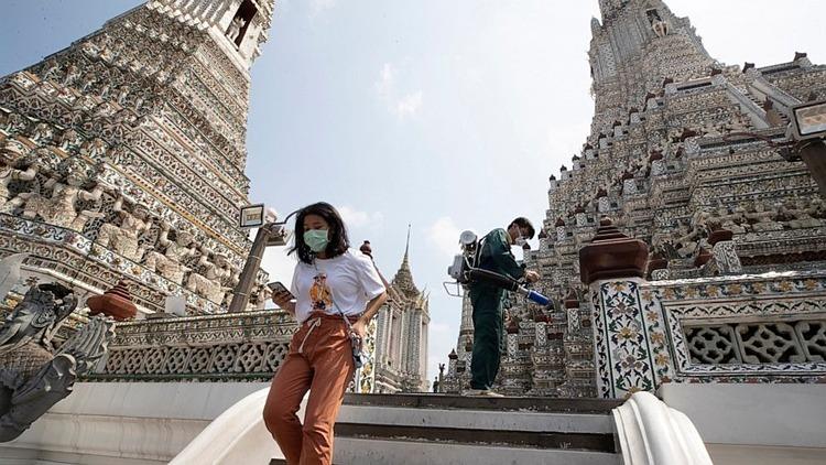 Khách du lịch đeo khẩu trang tham quan một ngôi chùa tại Bangkok trong lúc công nhân phun thuốc khử trùng ngày 12/3. Ảnh: AP