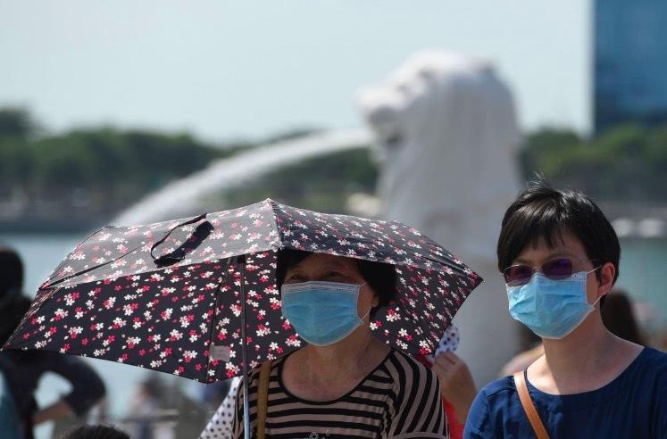 Hai du khách đeo khẩu trang ở Marina Bay (Singapore). Ảnh: AFP