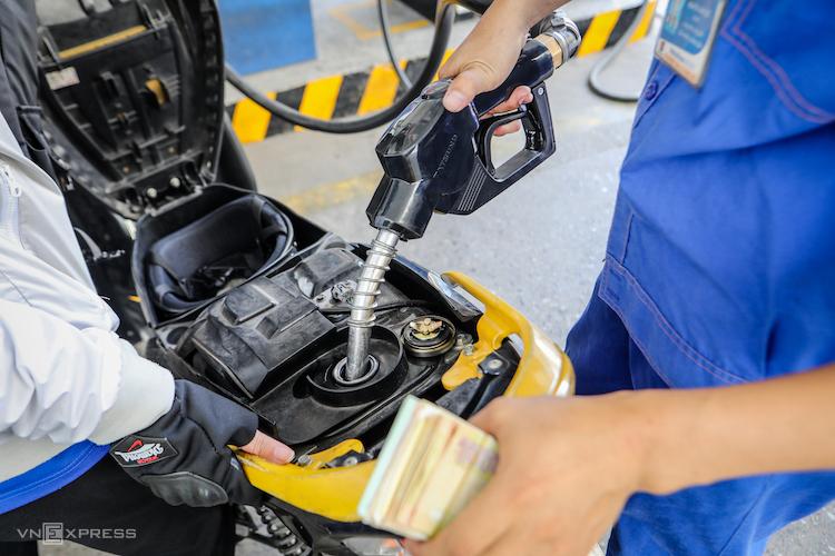Nhân viên cây xăng ở góc đường Lê Thánh Tôn (TP HCM) bơm xăng cho khách hàng. Ảnh: Nguyễn Thành
