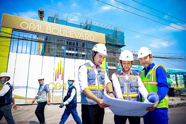 Các công nhân kiểm tra tiến độ xây dựng tại dự án.