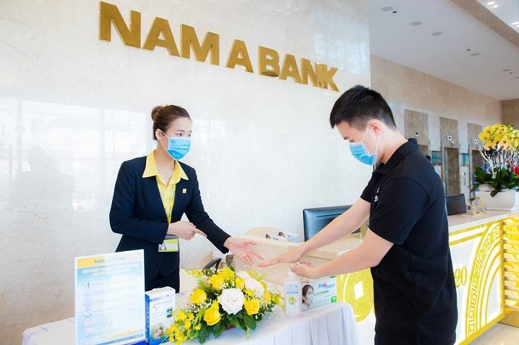 Khách hàng được phát khẩu trang và rửa tay sát khuẩn miễn phí trước khi giao dịch.