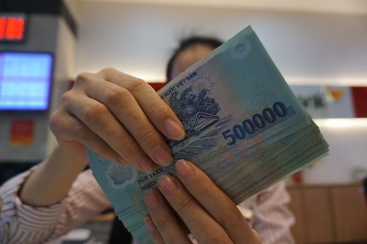 Khách hàng gửi tiền tại một ngân hàng thương mại. Ảnh: Anh Tú.