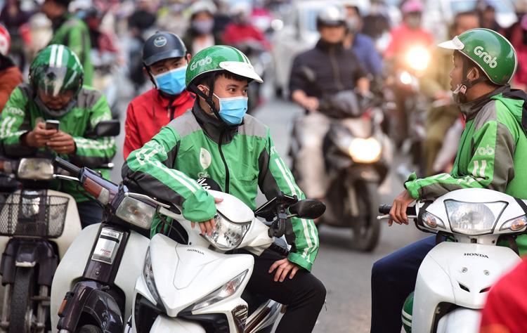 Tài xế xe ôm công nghệ đứng chờ khách trên đường Láng, Hà Nội chiều 2/1/2020 .Ảnh: Hoàng Phương