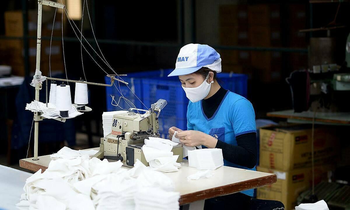 Công nhân làm thêm giờ để sản xuất khẩu trang. Ảnh: Cao Nam