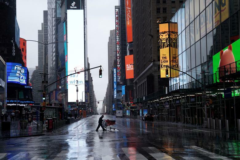Một người vô gia cư sang đường tại Quảng trường Thời đại vắng vẻ ở New York (Mỹ). Ảnh: Reuters