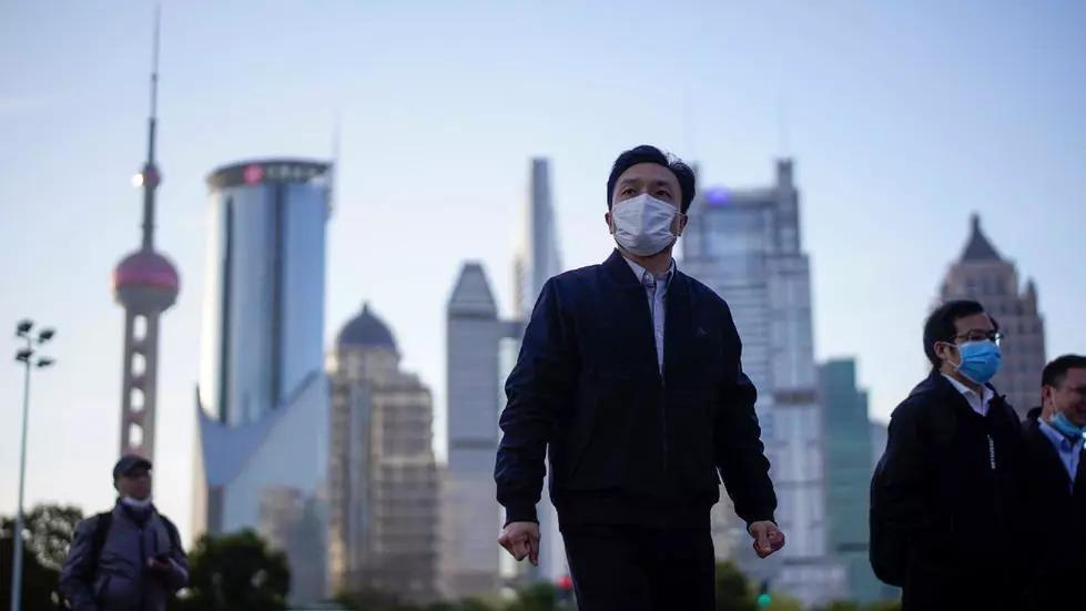 Người dân Trung Quốc đeo khẩu trang tại khu tài chính Lujiazui ở Thượng Hải ngày 19/3.Ảnh: Reuters.