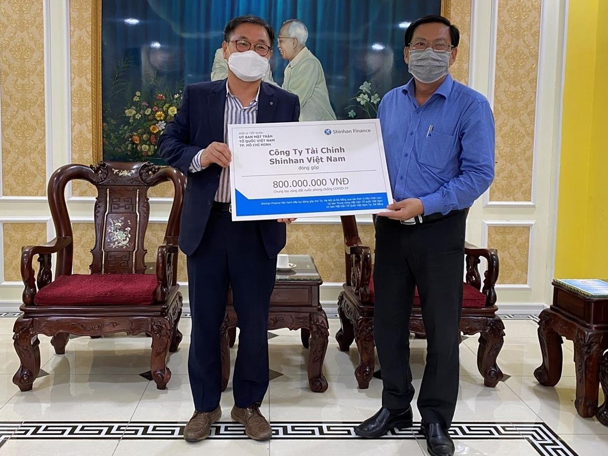 Ông Oh Tae Joon - Phó tổng giám đốc Shinhan Finance trao biểu trưng số tiền đóng góp 800 triệu đồng cho đại diện Ủy ban Mặt trận Tổ quốc Việt Nam TP HCM.