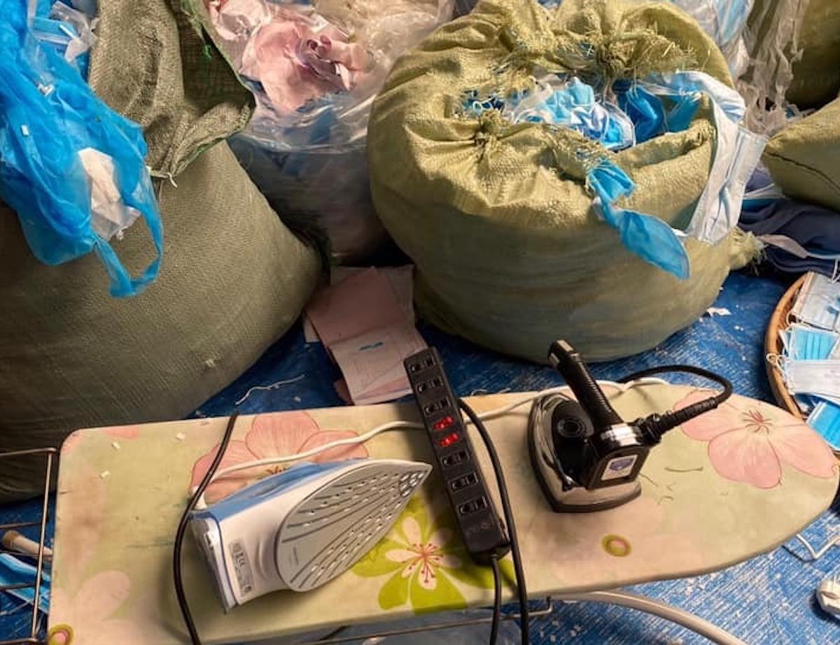 Khẩu trang y tế đã qua sử dụng được thu gom, đựng trong bao tải rồi dùng bàn là tái chế. Ảnh: QLTT Long An