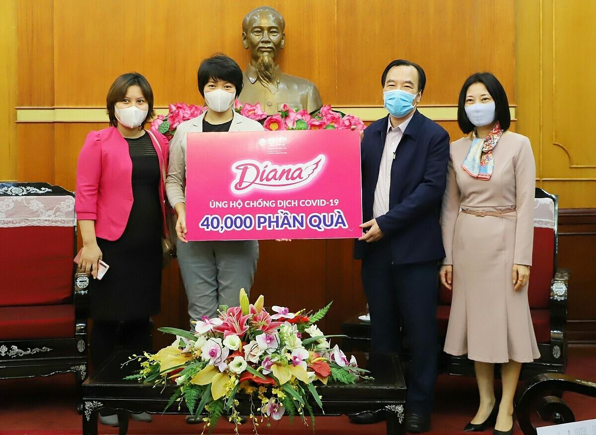 Bà Eriko Sato - Trưởng phòng Tiếp thị Người tiêu dùng của Diana Unicharm (thứ hai từ trái sang) trao tặng biểu trưng 40.000 phần quà tới đại diện Ủy ban Trung ương Mặt trận Tổ quốc Việt Nam.