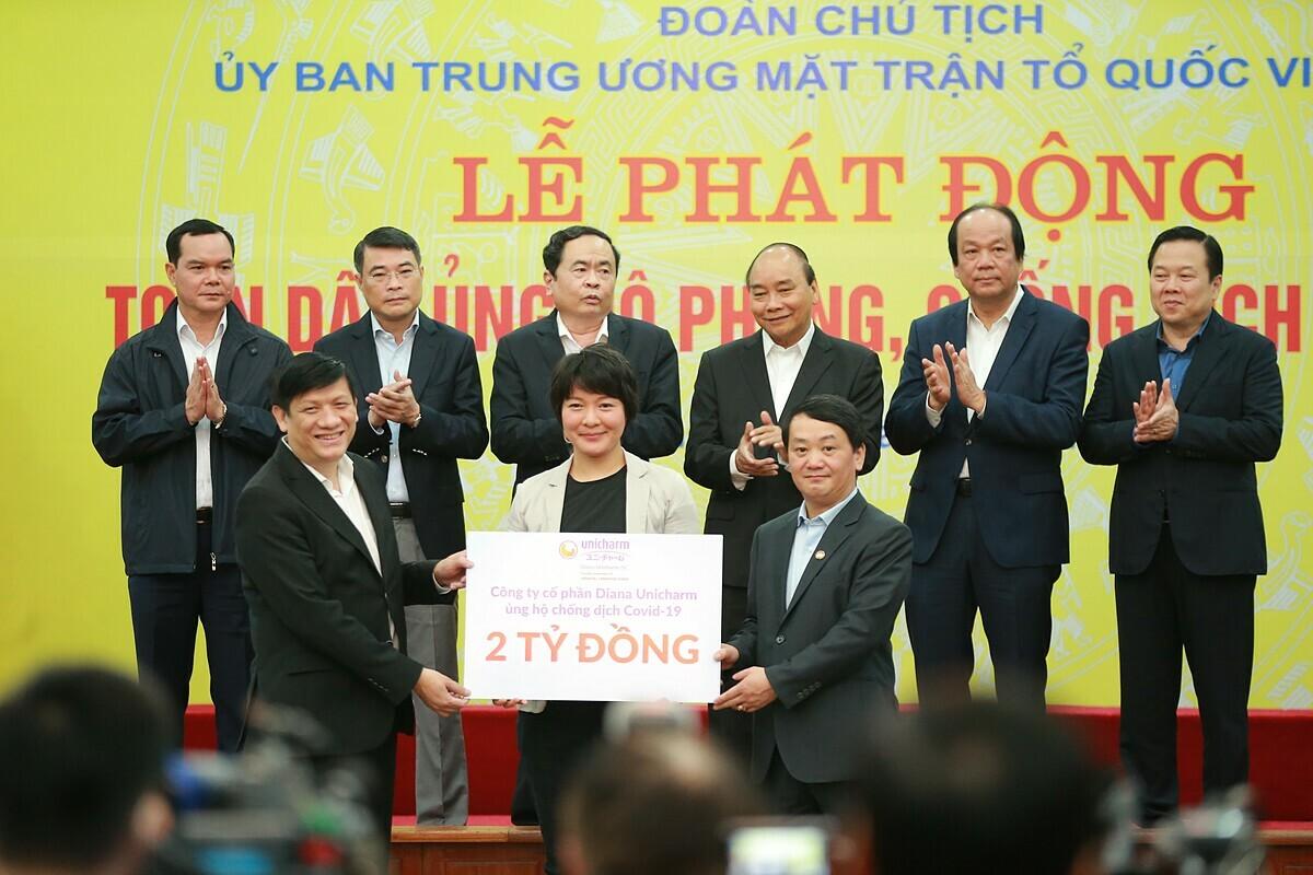 Bà Eriko Sato đại diện Diana Unicharm trao biểu trưng hai tỷ đồng ủng hộ chống dịch.