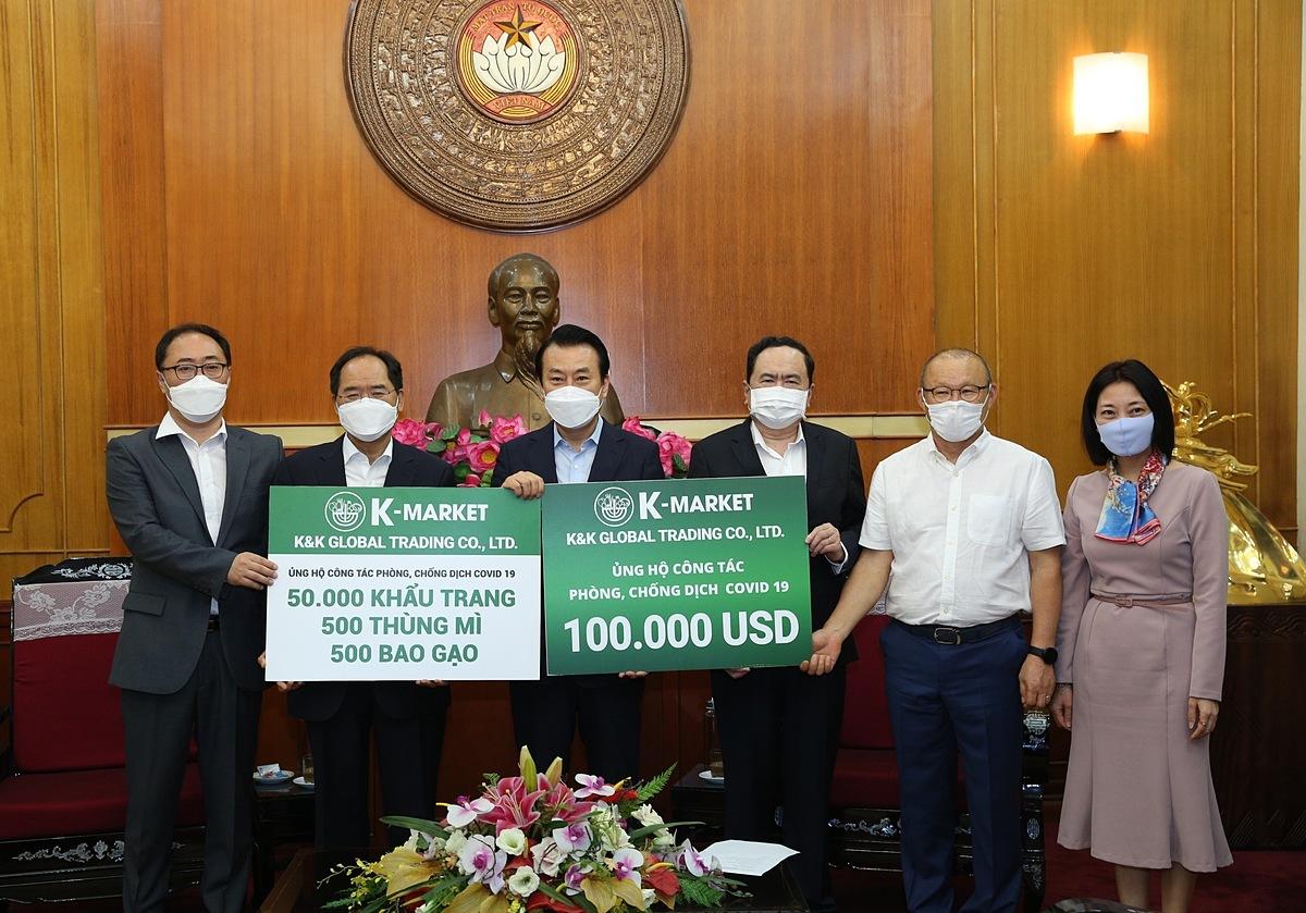 Đại diện công ty K&K sở hữu chuỗi bán lẻ K-Market tặng biểu trưng ủng hộ phòng chống Covid-19 cho đại diện Ủy ban trung ương Mặt trận Tổ quốc Việt Nam.
