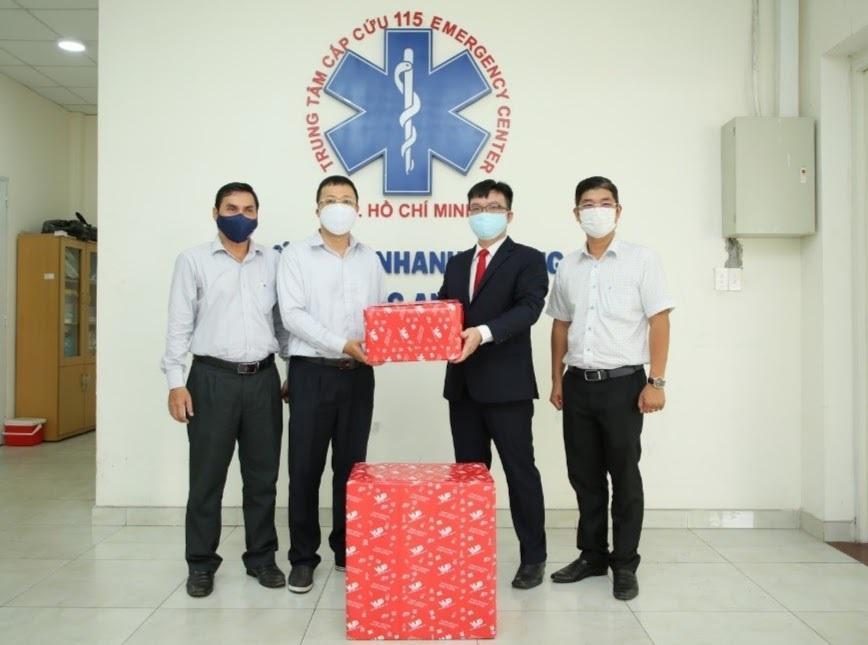 Ông Lưu Quốc Khang - Giám đốc Dịch vụ Học đường VUS tặng khẩu trang cho bác sĩ CKI Nguyễn Duy Long, đại diện Giám đốc Trung tâm cấp cứu 115 (thứ hai và thứ ba từ phải sang).