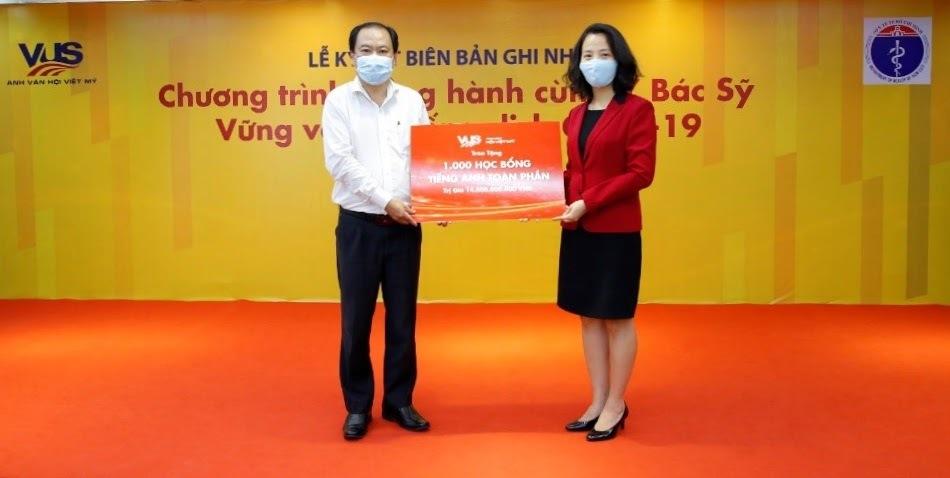 Đại diện VUS (phải) trao biểu trưng 1.000 suất học bổng tiếng Anh toàn phần hỗ trợ cán bộ, nhân y tế và người thân duy trì việc trau dồi ngoại ngữ.