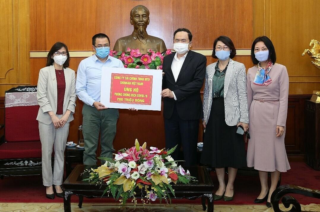 Ông Bảo Văn - Giám đốc Mạng lưới Chi nhánh Shinhan Finance (trái) trao biểu trưng số tiền đóng góp 200 triệu đồng cho ông Trần Thanh Mẫn - Chủ tịch Ủy ban Trung ương Mặt trận Tổ quốc Việt Nam ngày 3/4.