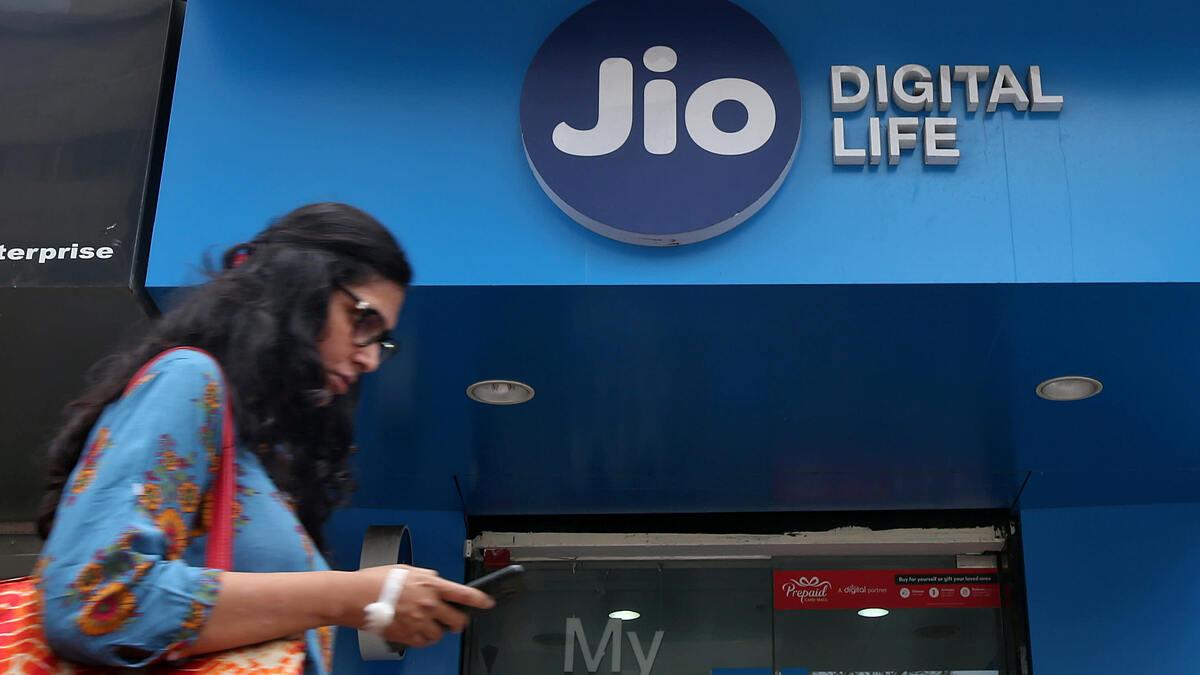 Một người phụ nữ đi ngang qua cửa hàng di động Jio Digital Life thuộc Tập đoàn Reliance Industries ở Mumbai (Ấn Độ). Ảnh: Reuters.